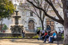 Early morning in central plaza, Antigua, Guatemala. Antigua, Guatemala - March 30, 2018: Early morning vendors, locals & tourists on Good Friday in central plaza stock photography