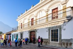White colonial house & Agua volcano slope in Antigua, Guatemala. Antigua, Guatemala - March 18, 2018: Lent procession spectators walk past colonial buildings & royalty free stock photo