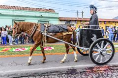 Roman chariot in Good Friday procession walks beside procession carpet, Antigua, Guatemala royalty free stock images