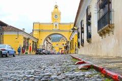Antigua miasto, Gwatemala Żółty łuk przy główną ulicą Kolonialni budynki i brukują kamienną ulicę zdjęcie stock
