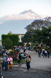 Antigua. People walk through Parque Central in Antigua, Guatemala with Volcán de Agua commanding the background view