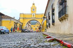 Antigua-Stadt, Guatemala Der gelbe Bogen an der Hauptstraße Kolonialbauten und Kopfsteinstein Straße stockfoto