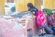 Antigua street laundry. ANTIGUA , GUATEMALA - JULY 30 : Guatemalan girl wash laundry in a traditional street washing facility in Antigua, Guatemala on July 30 royalty free stock photos