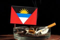 Antigua und Barbuda-Flagge mit brennender Zigarette im Aschenbecher lokalisiert auf Schwarzem Lizenzfreies Stockfoto