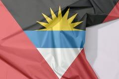 Antigua und Barbuda-Gewebeflaggenkrepp und -falte mit Leerraum lizenzfreie stockbilder