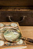 Antigue travelling objects. Travelling set - Vintage suitcase, magnifier and world map Stock Photography