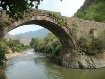 A antiguidade apedreja a ponte de Alaverdi com um rio e afinal as montanhas arménia Imagem de Stock Royalty Free