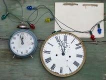 A antiguidade do ano novo cronometra no fundo de madeira da casca verde Bloco de notas vazio feito a mão de Kraft Modelo do feria Fotografia de Stock