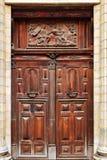 Antiguidade e porta dobro de madeira ornamentado de uma igreja velha com relevo religioso foto de stock