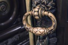 A antiguidade figurou o botão de porta de bronze em uma porta maciça imagem de stock royalty free
