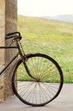 Antiguidade ou bicicleta oxidada retro fora em uma parede de pedra Fotografia de Stock Royalty Free