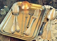 Antiguidades - a cutelaria, colheres, forquilhas, facas em uma bandeja, imagem é matizada Imagens de Stock Royalty Free