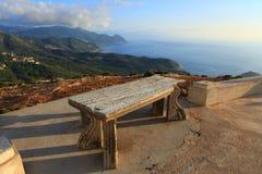 Antik bänk för sten på bakgrunden av gröna berg, moln och havslandskapet fotografering för bildbyråer