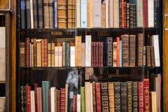 Antik böcker på den bruna bokhyllan arkivfoton