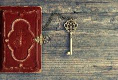 Antik bibelbok och guld- tangent på träbakgrund Arkivfoton