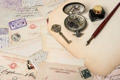 Antik bläckpenna, tangent, klocka, gamla vykort och bokstäver Royaltyfri Bild