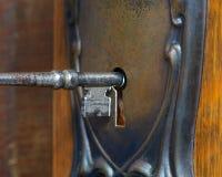 Antik dörr med den skelett- tangenten som går in i det key hålet Arkivfoton