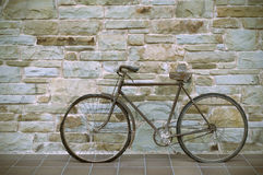Antik eller retro oxiderad cykel utanför på en stenvägg royaltyfri fotografi