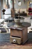 Antik fintelkaffekvarn på en kafébakgrund arkivbilder