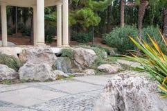 Antik gazebo i en parkera som omges av de sydliga växterna Arkivbilder