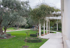 Antik gazebo i en parkera som omges av de sydliga växterna Royaltyfri Foto