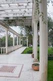 Antik gazebo i en parkera som omges av de sydliga växterna Royaltyfria Bilder