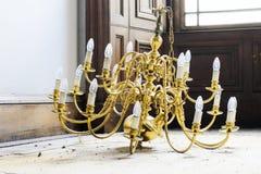 Antik guld f?r ljuskronaljus p? golvb?rgning som tas bort fr?n tak i konstruktionsplats arkivfoton