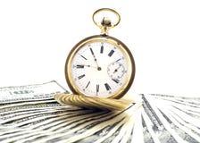 Antik guld- klocka på en bunt av isolerade pengardollar Royaltyfria Foton