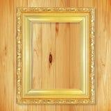 Antik guld- ram på träväggen; Tom bildram på woode Royaltyfria Bilder