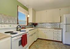 Antik kökinre med vita kabinetter och den gröna väggen arkivfoton