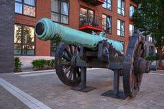Antik kanon som används som garnering på husutveckling som är närgränsande till flodThemsen royaltyfria foton