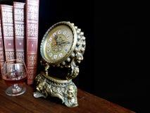 Antik klocka, en bok och ett exponeringsglas av konjak Arkivfoton
