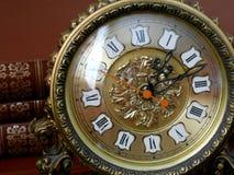 Antik klocka på en bakgrund av böckerna Royaltyfri Bild