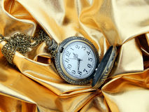 Antik klocka på en guld- bakgrund Royaltyfri Fotografi
