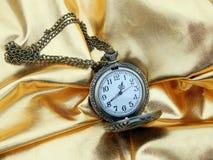 Antik klocka på en guld- bakgrund Arkivfoto