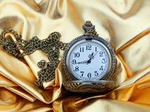 Antik klocka på en guld- bakgrund Royaltyfri Bild