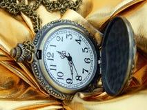 Antik klocka på en guld- bakgrund Arkivfoton
