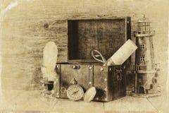 Antik kompass, bläckhorn och gammal träbröstkorg på trätabellen gammalt foto för svartvit stil Arkivfoton