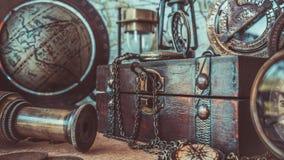 Antik kompass, klockahalsband, teleskop, träskattask och jordklotmodell Pirate Collection Photos arkivfoton