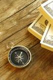 Antik kompass och pengar på den wood tabellen Fotografering för Bildbyråer