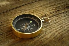 Antik kompass på den wood tabellen Royaltyfri Foto