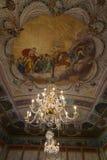 Antik ljuskrona på utsmyckat tak fotografering för bildbyråer