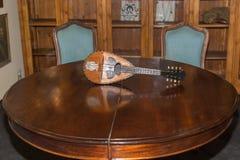 Antik mandolin på den trärunda tabellen med två stolar Royaltyfria Foton