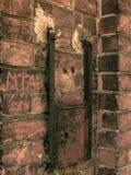 Antik metallask på en tegelstenvägg arkivfoto
