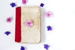 Antik pappers- bok och blommor på vit bakgrund arkivfoton