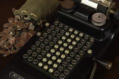 Antik räknemaskin med påsen av mynt Arkivbilder