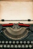 Antik skrivmaskin med det åldriga texturerade pappers- arket Arkivbild