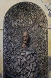 Antik springbrunn för sten i väggen av huset royaltyfri fotografi