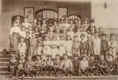 Antik stående av skolaklasskompisar Barn och lärare Royaltyfria Foton