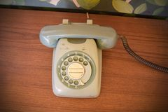 Antik telefon, Retro roterande telefon på den wood tabellen Arkivbild